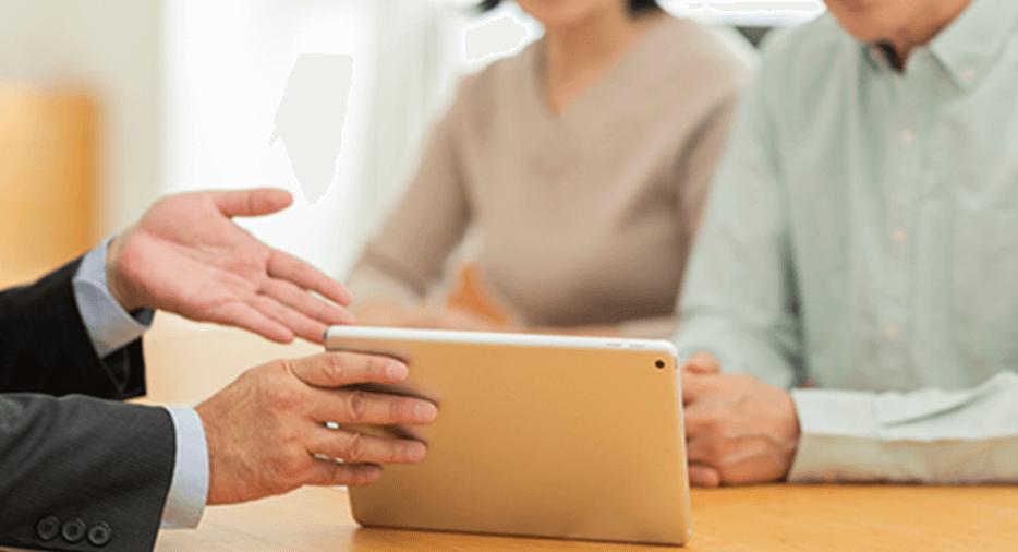 高齢者の夫婦がスーツを着た男性にタブレットで説明をうけている写真